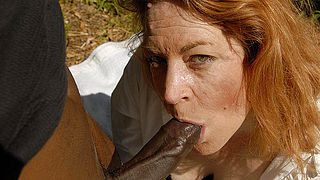 This red mama loves to swallow black cock