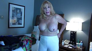 Busty mature puts on some clothes after posing nude